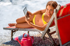 Woman using digital tablet on the sunbed Stock Photos
