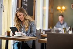 Woman Using Digital Tablet At Table Stock Image