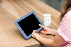 Woman using digital tablet by table at home Royalty Free Stock Photo
