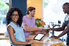 Woman using digital tablet while waiter serving coffee to man at counterWoman using digital tablet w Royalty Free Stock Photography