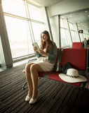 Woman using digital tablet while waiting for airplane departure Royalty Free Stock Images