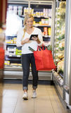 Woman Using Digital Tablet While Walking In Supermarket Royalty Free Stock Photo