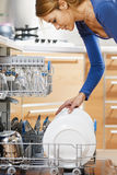Woman using dishwasher Royalty Free Stock Photo