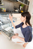 Woman using a dishwasher in a modern kitchen. royalty free stock photos
