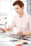 Woman using drawing pad. Young woman sitting at desk at work, using drawing pad and laptop, concentrating royalty free stock photography