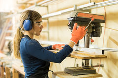 Woman using a drill press for work. Profile view of a young female carpenter using a drill press on a wood board in a woodshop Stock Images