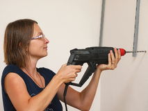 Woman using a drilling machine. Royalty Free Stock Photography