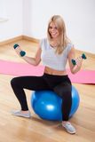 Woman using dumbbells and fitness ball Royalty Free Stock Image