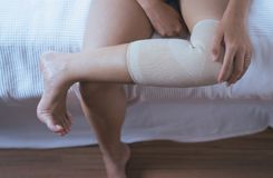 Woman using elastic bandage with legs having knee or leg pain,Female feeling exhausted and painful,Close up. Woman using elastic bandage with legs having knee or Stock Photo