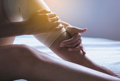 Woman using elastic bandage with legs having knee or leg pain,Female feeling exhausted and painful,Close up. Woman using elastic bandage with legs having knee or Royalty Free Stock Photos
