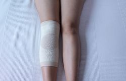 Woman using elastic bandage with legs having knee or leg pain,Female feeling exhausted and painful,Close up. Woman using elastic bandage with legs having knee or Royalty Free Stock Photography