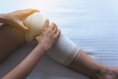 Woman using elastic bandage with legs having knee or leg pain,Female feeling exhausted and painful. On bedroom Stock Images