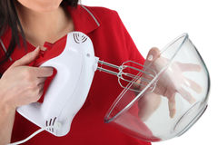 Woman using an electric beater. A woman using an electric beater royalty free stock image