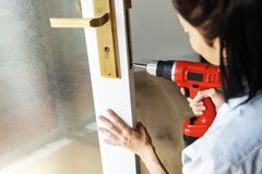 Woman using electric drill to fix the door Royalty Free Stock Photos