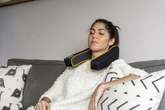 Woman with Electric Massage Cushion. Woman using Electric massage cushion with infrared warming areas royalty free stock images