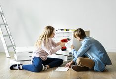 Woman using electronic drill install cabinet royalty free stock image