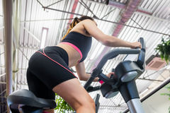 Woman using an exercise bike Stock Images