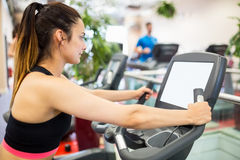 Woman using the exercise bike and looking at a small screen Royalty Free Stock Images