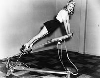 Woman using exercise equipment Stock Image