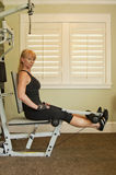 Woman using exercise machine. Attractive blond woman using exercise machine for leg lifts in a home gym Stock Photography