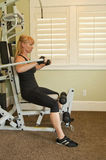 Woman using exercise machine. Attractive blond woman using exercise machine in a home gym Stock Photo