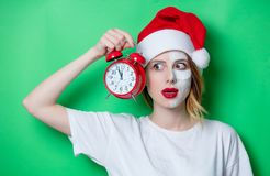 Woman using eye patch for her eyes in Santa Claus hat. With cream on her face and holding vintage alarm clock. Portrait of natural  and true female as usually Stock Photos
