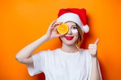 Woman using eye patch for her eyes in Santa Claus hat with cytru Royalty Free Stock Images