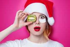 Woman using eye patch for her eyes in Santa Claus hat with Kiwi Royalty Free Stock Photography