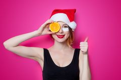 Woman using eye patch for her eyes in Santa Claus hat with orang Royalty Free Stock Photography