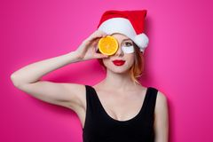Woman using eye patch for her eyes in Santa Claus hat with orang Royalty Free Stock Images