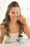 Woman using eyelash curler in bathroom Stock Photography