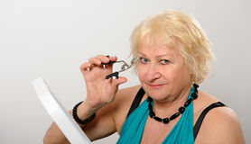 Woman using eyelash curler. Royalty Free Stock Images
