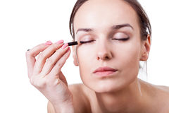Woman using an eyeliner Royalty Free Stock Photos
