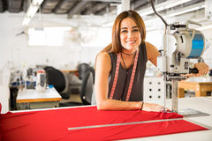 Woman using a fabric cutting machine. Portrait of a beautiful young brunette using a fabric cutting machine in a textile factory Royalty Free Stock Image