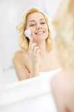 Woman using face cleansing brush. A picture of a young woman using face cleansing brush in the bathroom stock image