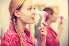 Woman using facial cleansing brush on face Stock Photography