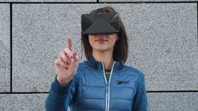 Woman using finger to touch on imaginary panel viewing on VR device outdoors. Augmented virtual reality concept.  stock footage