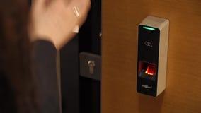 Woman is using fingerprint scanner. To open the door stock video footage
