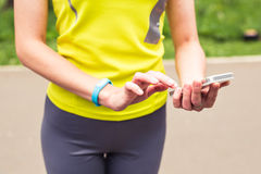 Woman using fitness bracelet during morning run Stock Images