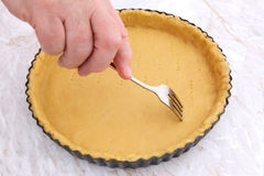 Woman using fork to prick holes in an uncooked pie crust Royalty Free Stock Images