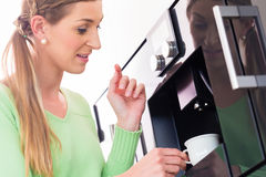 Woman using fully automatic coffee machine Stock Images