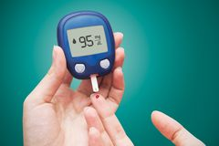 Woman using glucometer Stock Photo
