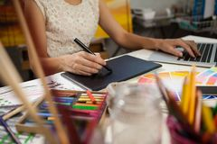 Woman using graphic tablet and laptop in drawing class. Mid-section of woman using graphic tablet and laptop in drawing class stock photography