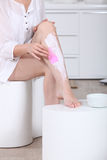Woman using hair removal cream Stock Images