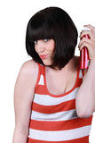 Woman using hair spray. Brunette woman using hair spray Royalty Free Stock Images