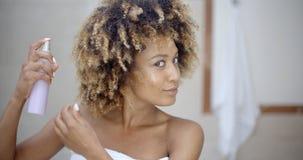 Woman Using Hair Spray In Bathroom Stock Image