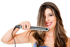 Woman using a hair straightener Royalty Free Stock Photo