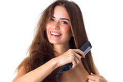 Woman using hair straightener Royalty Free Stock Image