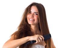 Woman using hair straightener Stock Image
