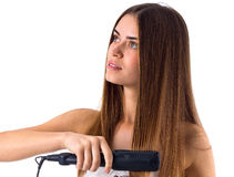 Woman using hair straightener Royalty Free Stock Photography